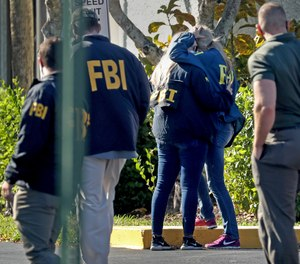 FBI agents console each other as they arrive at the Broward County Medical Examiner's Office in Dania, Fla., after two FBI agents were killed and three wounded while trying to serve a search warrant in Broward County on Tuesday Feb. 2, 2021.