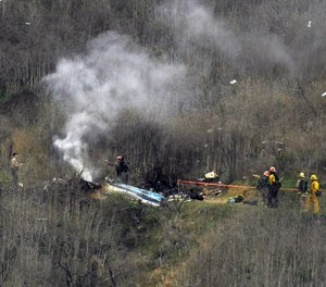 In this Jan. 26, 2020, file photo, firefighters work the scene of a helicopter crash in Calabasas, Calif.