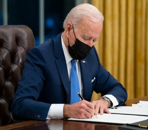 President Joe Biden signs an executive order on immigration in the Oval Office of the White House in Washington.