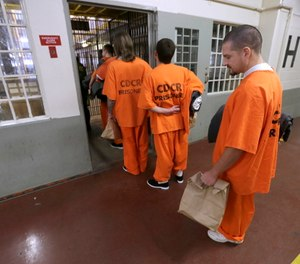 Inmates wait to enter their assigned cell block after arriving at the Deuel Vocational Institution in Tracy, Calif.