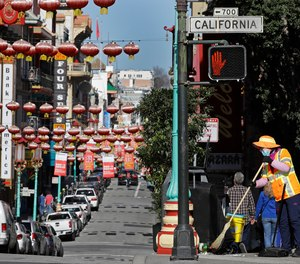 n this Jan. 31, 2020, file photo, a masked worker cleans a street in the Chinatown district in San Francisco.