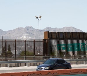 A car drives on a highway parallel to a border fence in El Paso, Texas.