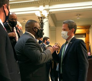 Georgia Gov. Brian Kemp, right, bumps fists with Democratic state Rep. Carl Gilliard of Garden City on Tuesday, Feb. 16, 2021, at the state Capitol in Atlanta.