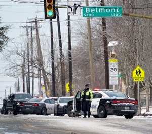 A Dallas police presence is seen at the street intersection of Belmont and Henderson in a neighborhood where earlier in the day two other officers were shot responding to an emergency call in Dallas, Thursday, Feb. 18, 2021.