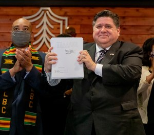 Flanked by lawmakers and supporters, Gov. J.B. Pritzker signs a sweeping criminal justice reform bill into law during a ceremony at Chicago State University on the South Side, Monday, Feb. 22, 2021.