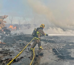 A firefighter battles a fire at at commercial yard in Compton, Calif., on Friday, Feb. 26, 2021. A huge fire visible across Los Angeles burned material in a commercial yard and parked buses early Friday.