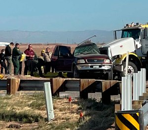 In this image from KYMA law enforcement work at the scene of a deadly crash involving a semitruck and an SUV in Holtville, Calif., on Tuesday, March 2, 2021.