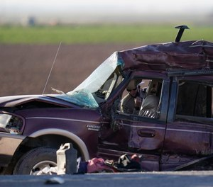 A California Highway Patrol officer examines the scene of a deadly crash in Holtville, Calif., Tuesday, March 2, 2021.