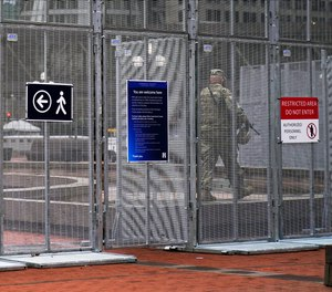 A National Guard soldier walks inside the fenced-off plaza of the Hennepin County Government Center, Wednesday, March 10, 2021, in Minneapolis where the trial for former Minneapolis police officer Derek Chauvin continues with jury selection.