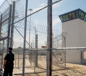 A correctional officer walks near one of two entrances into Kern Valley State Prison, in Delano, Calif.