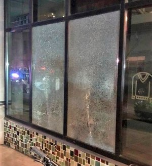 This Friday, March 12, 2021, photo released by Portland Police Bureau shows shmashed windows left behind by people inside the perimeter of a march by a group of about 100 hundred protesters Friday night in Portland, Ore.