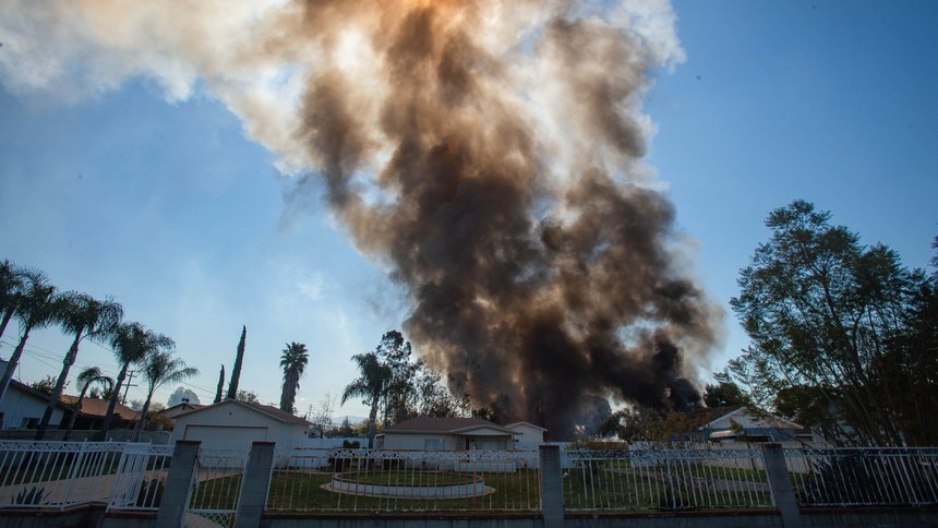 Smoke rises in the background after a fireworks stash exploded in Ontario, Calif.