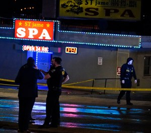 Law enforcement officials confer outside a massage parlor following a shooting on Tuesday, March 16, 2021, in Atlanta. (AP Photo/Brynn Anderson)