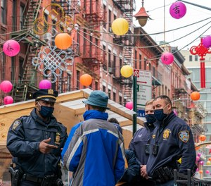 In this March 17, 2021, file photo, Capt. Tarik Sheppard, left, Commander of the New York Police Department Community Affairs Rapid Response Unit speaks to a resident while on a community outreach patrol in the Chinatown neighborhood of New York.