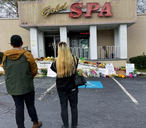 Flowers, candles and signs are displayed at a makeshift memorial on Friday, March 19, 2021, in Atlanta.