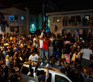 Crowds defiantly gather in the street while a speaker blasts music an hour past curfew in Miami Beach, Fla., on Sunday, March 21, 2021.