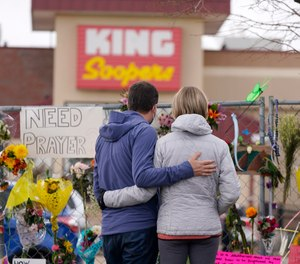 Mourners walk the temporary fence line outside the parking lot of a King Soopers grocery store, the site of a mass shooting in which 10 people died, Friday, March 26, 2021, in Boulder, Colo.