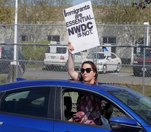 A protester holds a sign she looks out from the sunroof of a car during a protest at the Northwest Detention Center, a facility privately operated on behalf of the U.S. Immigration and Customs Enforcement agency, in Tacoma, Wash.