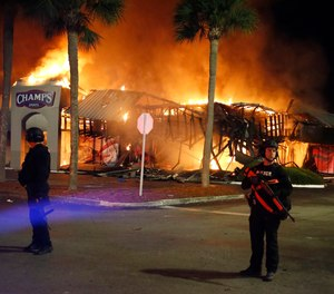 SWAT officers guard firefighters as they respond to the Champs Sports store, Sunday, May 31, 2020 in Tampa. A Florida man was convicted Tuesday, March 30, 2021 of setting fire to the store during unrest that followed protests over the death of George Floyd.