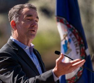 In this March 30, 2021, file photo, Virginia Gov. Ralph Northam speaks at a news conference to announce the expansion of commuter rail in Virginia at the Amtrak and Virginia Railway Express (VRE) Alexandria Station, in Alexandria, Va.