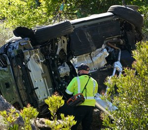 In this Feb. 23, 2021, file photo a vehicle rests on its side after a rollover accident involving golfer Tiger Woods, in Rancho Palos Verdes, Calif., a suburb of Los Angeles.