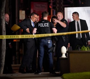 Investigators gather outside an office building where a shooting occurred in Orange, Calif., Wednesday, March 31, 2021.