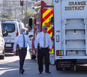Officials work outside the scene of a shooting, Thursday, April 1, 2021 in Orange, Calif.
