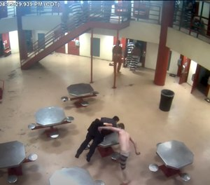 In this Saturday, March 27, 2021, image taken from video released Friday, April 2, 2021, by the Oklahoma City Police Department from the Oklahoma County Detention Center, an officer is attacked by an inmate before police shoot and kill another inmate who was holding a homemade knife to the officer's neck.