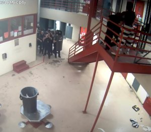 In this Saturday, March 27, 2021, image taken from video released Friday, April 2, 2021, by the Oklahoma City Police Department from the Oklahoma County Detention Center, an officer is attacked by an inmate, upper right, before being shot and killed by police while holding a homemade knife to the officer's neck.