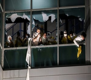 Inmates, from a second cell block, cough and try to breathe through broken windows after officers deploy a chemical irritant at the St. Louis Justice Center.