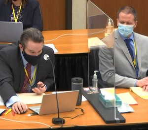 In this image from video, defense attorney Eric Nelson, left, and defendant, former Minneapolis police Officer Derek Chauvin, right, listen as Hennepin County Judge Peter Cahill presides in the trial of Chauvin, Tuesday, April 6, 2021, at the Hennepin County Courthouse in Minneapolis.