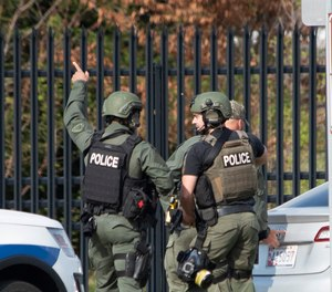 Members of the Frederick Police Department Special Response Team prepare to enter Fort Detrick at the Nallin Farm Gate following a shooting in Riverside Tech Park in Frederick, Md. Authorities say a Navy medic shot two U.S. sailors before fleeing to the Army base, where he was shot and killed.