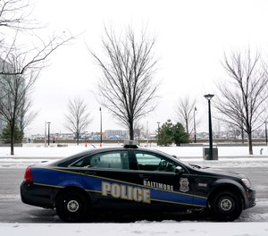 In this Thursday, Feb. 18, 2021, file photo, a Baltimore police cruiser is seen parked near a building while officers check on a call.