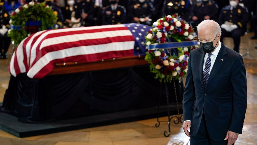 """President Joe Biden stands as a joint services honor guard carries the flag-draped casket of U.S. Capitol Police officer William """"Billy"""" Evans, to where he will lie in honor at the Capitol in Washington, Tuesday, April 13, 2021."""