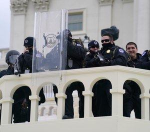 In this Wednesday, Jan. 6, 2021, photo, U.S. Capitol Police officer stand as rioters storm the Capitol in Washington, D.C.