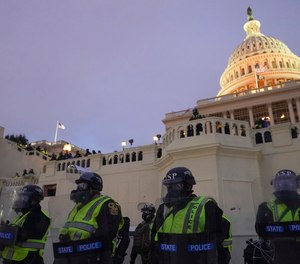 In this Wednesday, Jan. 6, 2021, photo, police form a line to guard the Capitol after violent rioters stormed the Capitol, in Washington.