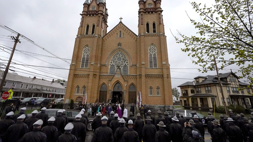 """Members of the Massachusetts state police, below, line the street as mourners for the late U.S. Capitol Police officer William """"Billy"""" Evans, depart St. Stanislaus Kostka Church following a funeral Mass, in Adams, Mass., Thursday, April 15, 2021."""