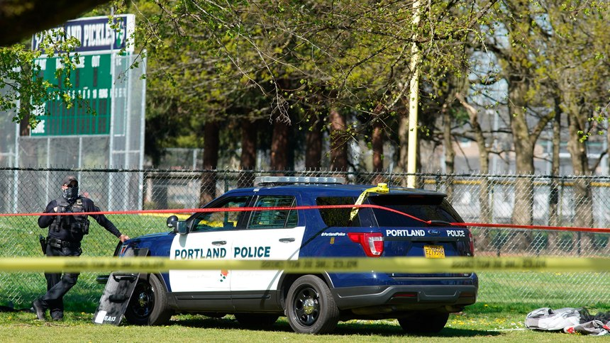 A Portland Police officer stand by following a police involved shooting of a man at Lents Park, Friday, April 16, 2021, in Portland, Ore.