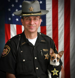 This 2006 image shows then Sheriff Dan McClelland and his small police dog Midge at the Geauga County, Ohio, sheriff's department. Both died on Wednesday, April 14, 2021.