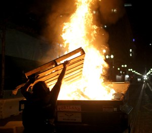Protesters light a fire in a dumpster in downtown Portland, Ore., Friday, April 16, 2021.