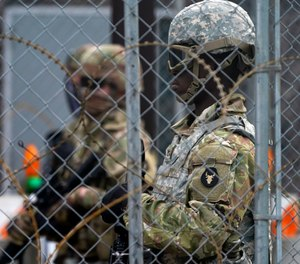 National Guard members are seen through fencing and wire near the Minneapolis Police 3rd Precinct in Minneapolis on Monday, April 19, 2021, after the murder trial against former police Officer Derek Chauvin advanced to jury deliberations.