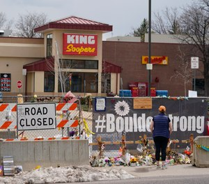 Tributes cover the temporary fence around the King Soopers grocery store in which 10 people died in a mass shooting in late March on Friday, April 23, 2021, in Boulder, Colo.