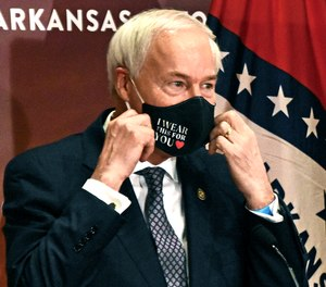This July 20, 2020 file photo shows Arkansas Gov. Asa Hutchinson removes at a briefing at the state capitol in Little Rock.