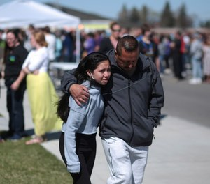 People embrace after a school shooting at Rigby Middle School in Rigby, Idaho on Thursday, May 6, 2021.