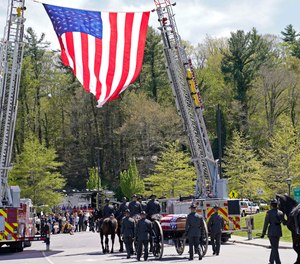 A processional approaches the Holmes Convocational Center for the funeral services of Watauga County Sheriff's Deputies Sgt. Chris Ward and K-9 Deputy Logan Fox in Boone, N.C., Thursday, May 6, 2021.