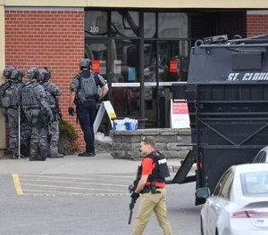 Officers stand near an entrance to the Wells Fargo branch Thursday May 6, 2021, in south St. Cloud, Minn. following a reported hostage situation. Police in Minnesota were on the scene Thursday of a reported bank robbery with hostages.