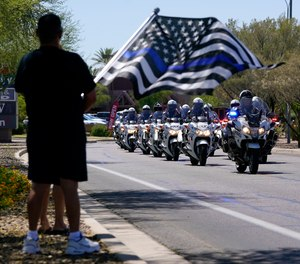 People line the streets as the body of Chandler Police Officer Christopher Farrar, killed in the line of duty is escorted during a large multi-jurisdiction police procession Friday, May 7, 2021, in Chandler, Ariz.