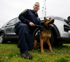 Virginia State Police K-9 officer Tyler Fridley, poses with his dog Aries at State Police headquarters in Richmond, Va., Monday, May 10, 2021.