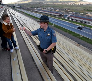Colorado State Patrol Trooper Josh Lewis fist bumps 3-year-old Lincoln Delagarza, of Northglenn, Colorado, before racing begins at Bandimere Speedway west of Denver on May 5, 2021.