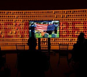 Relatives and law enforcement officers watch a virtual ceremony honoring the fallen law enforcement officers from 2020 during a reception commemorating the National Police Week at the National Law Enforcement Museum in Washington, Thursday, May 13, 2021.